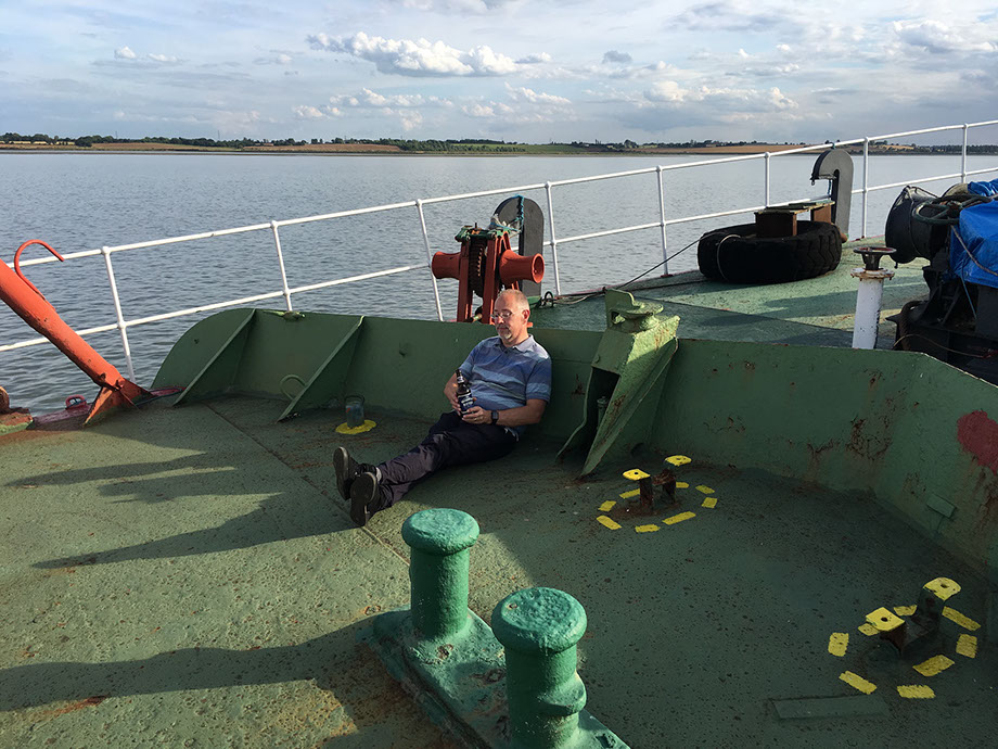 Keith, G6NHU sitting on the front of the ship with a bottle of beer, shortly after GB5RC went on air from Ross Revenge, home of Radio Caroline.